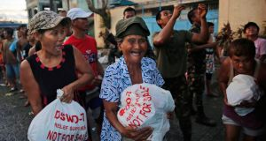 Residents of Tacloban receive food aid from the Philippines army. Photograph: Kevin Frayer/Getty Images