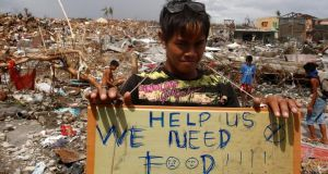 A typhoon survivor holds a placard asking for food while standing amid the ruins of houses destroyed by super typhoon Haiyan in Tanauan, Leyte, in central Philippines. Photograph: Reuters/Erik De Castro