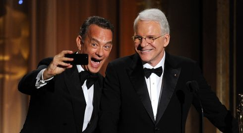 Tom Hanks takes a selfie with Steve Martin. Photograph: Kevin Winter/Getty Images