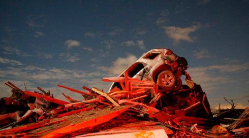 A car sits on a pile of debris from the destruction caused by a tornado that touched down in Washington, Illinois, on November 17th, 2013. A fast-moving storm system triggered multiple tornadoes, causing deaths and flattening large parts of the city of Washington, Illinois as it tore across the Midwest. The car bears a spraypaint mark to show it has been checked for casualties. Photograph: Jim Young/Reuters