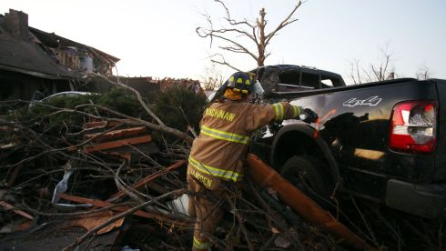 Jeremy Janssen of Mackinaw Fire Department marks a vehicle among the debris. Photograph: Tasos Katopodis/Getty Images