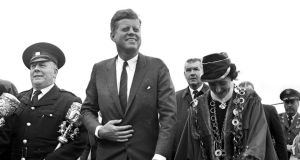 John F Kennedy, accompanied by the mayor of Limerick, Frances  Condell, walks towards the platform at Greenpark Racecourse, Limerick.