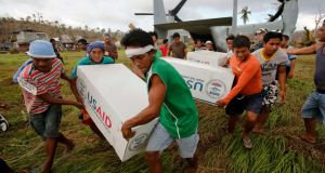 Filipinos carry boxes with aid from the US relief organisation US Aid in a remote village near the eastern Samar town of Guiuan yesterday.  Photograph: Wolfgang Rattay / Reuters