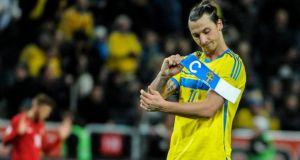 Sweden captain Zlatan Ibrahimovic takes off the armband after defeat to Portugal on Tuesday night.  Photograph: Erik Martensson/EPA