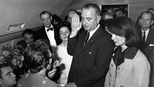 Judge Sarah T. Hughes administers the Presidential Oath of Office to then acting US President Lyndon Baines Johnson aboard Air Force One at Love Field in Dallas Texas. Johnson's wife, Lady Bird Johnson, and Jacqueline Kennedy, listen along with other witnesses.  Photograph: Cecil Stoughton/The White House/John F. Kennedy Presidential Library/Reuters