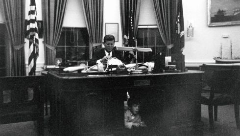 John F. Kennedy sits at his desk in the Oval Office while his son, John F. Kennedy Jr, looks out from underneath, at the White House in Washington in this handout image taken on October 17th, 1963, just a month before he was assassinated in Dallas.  Photograph: Cecil Stoughton/The White House/John F. Kennedy Presidential Library/Reuters
