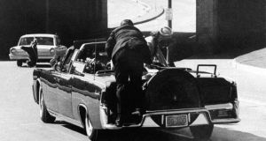 "President Kennedy slumps down in the back seat of the presidential limousine as it speeds along Elm Street toward the Stemmons Freeway overpass in Dallas after being fatally shot. First lady Jackie  Kennedy leans over the president as Secret Service agent Clint Hill pushes her back to her seat. Photgraph: James W. ""Ike"" Altgens/AP"