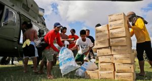 Residents of the destroyed island of Homonhon, near Taclabon, offload the first batch of food aid from an army helicopter in the aftermath of Typhoon Haiyan. Photograph:  Kevin Frayer/Getty Images