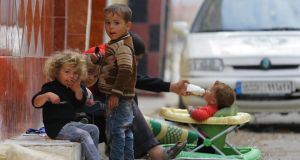 Children sit in the street as a baby drinks milk in the Duma neighbourhood of Damascus. Photograph: Bassam Khabieh/Reuters