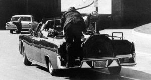 "Then secret service agent Clint Hill on the back of the president's car after the shooting. Photograph: James W ""Ike"" Altgens/AP"