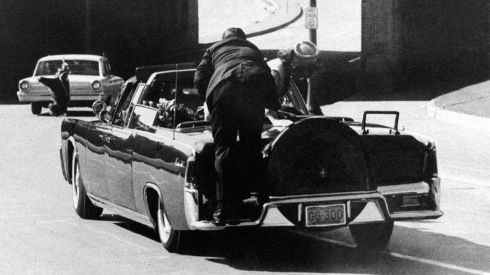 JFK slumps in the back seat of the presidential limousine after being shot as it speeds along Elm Street toward the Stemmons Freeway overpass in Dallas.  Mrs Kennedy leans over the president as Secret Service agent Clinton Hill jumps on the back of the car.  Photograph: Ike Altgens/AP Photo