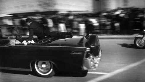 The limousine carrying a mortally wounded JFK races toward a hospital after his shooting. Agent Clinton Hill is riding on the back. Photograph: Justin Newman/AP Photo