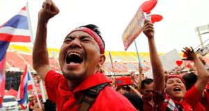 A Red-Shirt pro-Thaksin supporter shouts slogans during a rally to support the Thai government at Rajamangala National Stadium in Bangkok. Photograph: Rungroj Yongrit