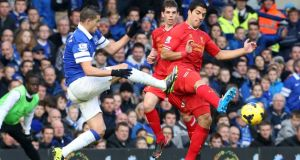 Everton's Kevin Mirallas (left) catches Liverpool's Luis Suarez with a high tackle  at Goodison Park. Photograph:  Peter Byrne/PA Wire