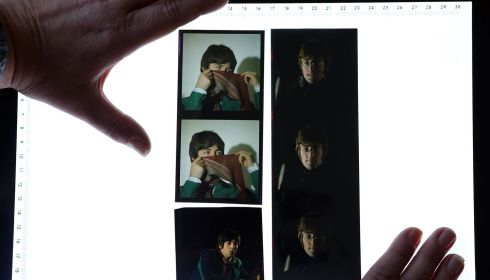 Omega Auctions salesroom manager Karen Fairweather lays out some of the unseen and unpublished images of The Beatles which are to be auctioned on Friday in Stockport. Photograph:   Dave Thompson/PA Wire