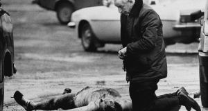 Fr Alec Reid praying over the body of one of the murdered soldiers. Photograph: Trevor McBride