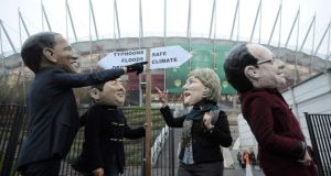 Protesters wearing leaders' masks demonstrate in front of the National Stadium during the UN Climate Change Conference  in Warsaw. Photograph: EPA/BartlomieJ Zborowski