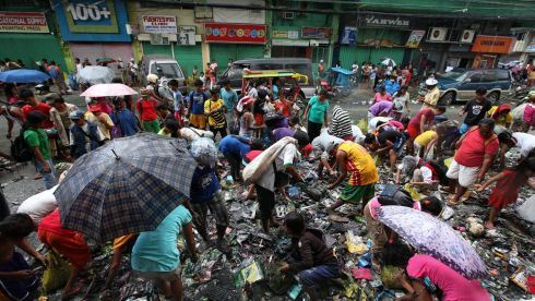 Filipino typhoon victims look for reusable material thrown out during the ongoing clean up in  the devastated city of Tacloban today. Photograph: Dennis M. Sabangan/EPA