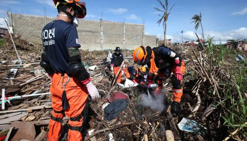 Members of a South Korean disaster team search for bodies in the devastated city of Tacloban today. Photograph: Dennis M. Sabangan/EPA