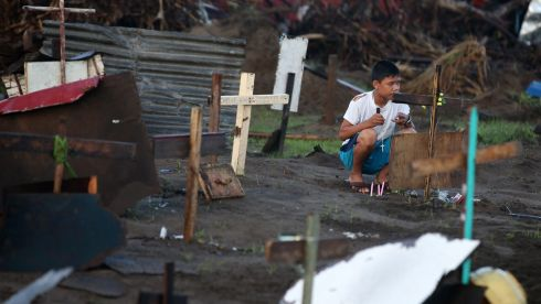 Randolph Lagrama (13) prays at the gravesite of his three relatives at a mass grave of typhoon victims in Palo, Leyte province  today. Photograph: Dennis M. Sabangan/EPA