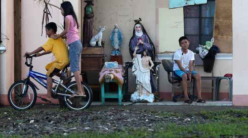 A Filipino boy cycles past sets of religious icons recovered from damaged church in Palo, Leyte province. Photograph: Dennis M. Sabangan/EPA
