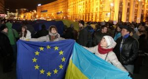 Activists hold European Union and Ukrainian flags during a meeting to support EU integration at European Square in Kiev on Tuesday. Photograph: Sergei Chuzavkov/AP