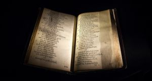 A copy of the Bay Psalm Book sits in a display case at Sotheby's auction house in New York last week. Published in 1640, the Bay Psalm Book is considered the first book printed in what was then the British colonies of North America. Photograph: Carlo Allegri/Reuters