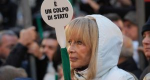A demonstrator holds a sign reading 'It is a coup of State' during a rally in support of Silvio Berlusconi in front of his house, Palazzo Grazioli, in Rome yesterday. Photograph: Giorgio Cosulich/Getty Images