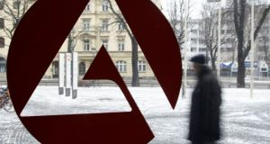 A man walks behind the labour office sign of an unemployment center in Munich. Photograph: Michaela Rehle/Reuters