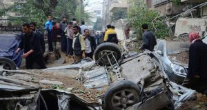 Residents gather near damaged cars at a site hit by what activists say was an airstrike by forces loyal to Syria's President Bashar al-Assad, near a children's park in Duma neighbourhood of Damascus. Photograpgh: Yousef Albostany/Reuters