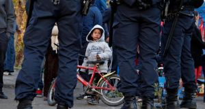 A Roma child looks at French police standing guard as Roma families are evicted from an illegal camp near the Var river in Nice, southeastern France. There are only 20,000 Roma in France but they are highly visible in shanty towns around Paris, Lille and Lyon. Photograph: Eric Gaillard/Reuters
