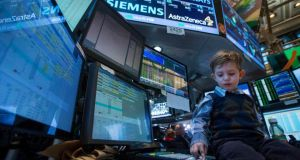 A young boy works at a trading post on the floor of the New York Stock Exchange yesterday. Traders traditionally bring their children to work for the half day of trading on the day after the Thanksgiving holiday. Photograph: Reuters/Brendan McDermid