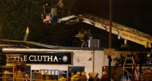 Rescue workers examine the wreckage of a police helicopter, which crashed onto the roof of the Clutha Vaults pub in Glasgow last night. Photograph: Russell Cheyne/Reuters