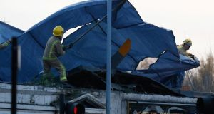 Rescue workers cover the wreckage of a police helicopter which crashed onto the roof of the Clutha Vaults pub in Glasgow last night. Photograph: Russell Cheyne/Reuters