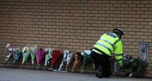 A police officer lays flowers near the scene of a helicopter crash in Glasgow city centre. Photograph: Andrew Milligan/PA Wire