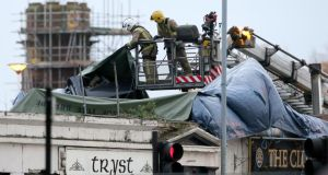 Members of the emergency services covering a piece of the helicopter on the roof of the Clutha Bar yesterday.  Photograph: Andrew Milligan/PA Wire