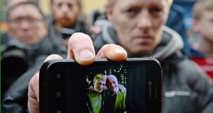 John McGarrigle junior, son of 60-year-old John McGarrigle senior, shows a camera phone picture of himself and his father, as he fears for his father's well-being, who is missing after the Glasgow helicopter crash. Photograph: Jeff J Mitchell/Getty Images