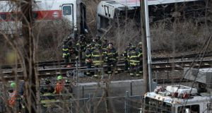 Firefighters and rescue personnel on the scene of a reported fatal passenger train derailment near the Spuyten Duyvil station in the Bronx neighbourhood of New York. Photograph: Andrew Gombert/EPA