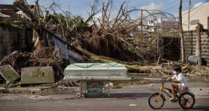 A young boy cycles past a coffin amid scenes of devastation in the aftermath of Typhoon Haiyan  in Tacloban, Philippines. Photograph: Kevin Frayer/Getty Images)