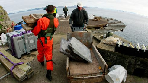 OPW worker brings materials for restoration work onto Skellig Michael as a member of the Air Corps prepares material for return to the main land. Photograph: Brian Lawless/PA Wire
