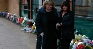 Survivors Nancy Primrose (left) and Ann Faulds walk away after placing a bouquet near the site of a police helicopter crash on to a pub in central Glasgow, yesterday. Photograph: Andrew Winning / Reuters