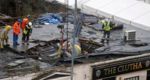 Rescue workers prepare to lift the wreckage of a police helicopter that crashed into a pub in central Glasgow. Photograph: Reuters