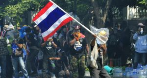 A Thai anti-government protester waves a Thai flag in a face off with riot police officers as the demonstrators try and reach to the Metropolitan Police Bureau in Bangkok, Thailand, today. Photograph: Narong Sangnak/EPA.