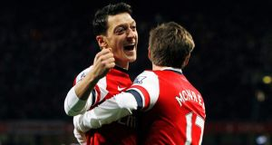 Arsenal's Mesut Ozil (left) celebrates with his teammate Nacho Monreal after scoring against Hull at the Emirates Stadium