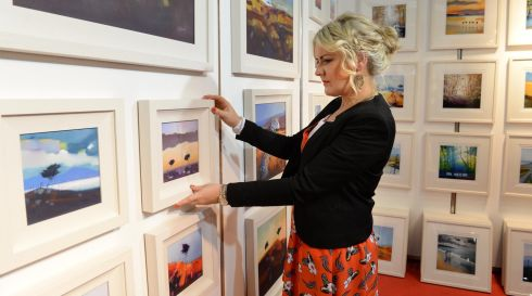 Artist Sharon McDaid of Donegal adjusts her oil paintings and prints at the National Crafts & Design Fair. Photograph: Dara Mac Dónaill/The Irish Times