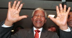 ANC leader Nelson Mandela raises his hands to ask everyone to respect security as he moves through a group of supporters at the Johannesburg Stock exchange, in this April 22, 1994 file photo. Photograph: Corinne Dufka/Files/Reuters.