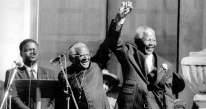 In Cape Town, Desmond Tutu joins hands with Nelson Mandela in triumph after the latter was proclaimed president of South Africa in 1994.