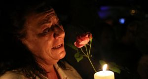 A women cries as she holds a candle and a flower outside former South African President Nelson Mandela's house in Houghton, last night. Photograph: Siphiwe Sibeko/Reuters.