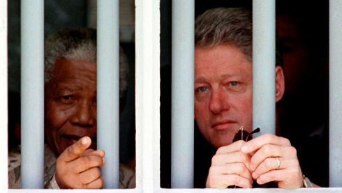 The US president Bill Clinton and South African president Nelson Mandela peer through the bars of the cell on Robben Island in 1998. REUTERS/Stringer/Files