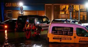 Coastguard rescue workers check vehicles in a flooded car wash during a storm surge in Great Yarmouth, south east England. Photograph: Darren Staples/Reuters